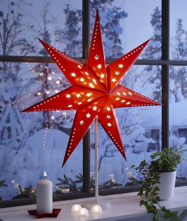 Rozsvícená červená vánoční hvězda za oknem