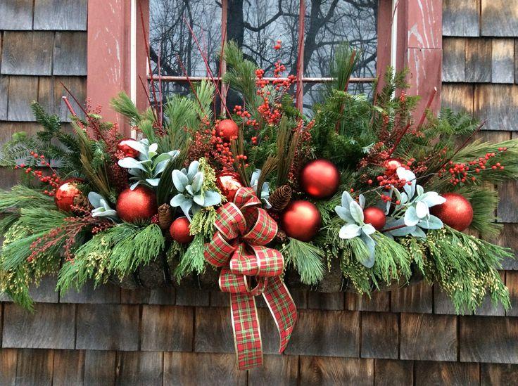 Vánoční venkovní truhlík ozdobený zelenými větvičkami a červenými baňkami