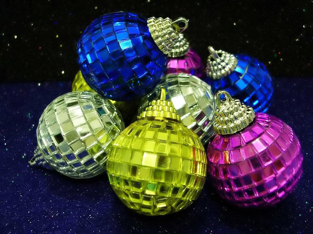 Růžové, modré a žluté ležící baňky, připomínající disco koule.