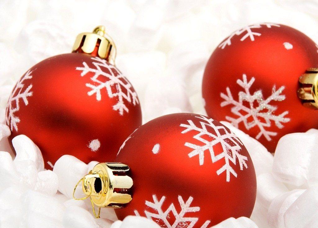 Vánoční obrázek s červenými ležícími baňkami ozdobenými bílými vločkami.