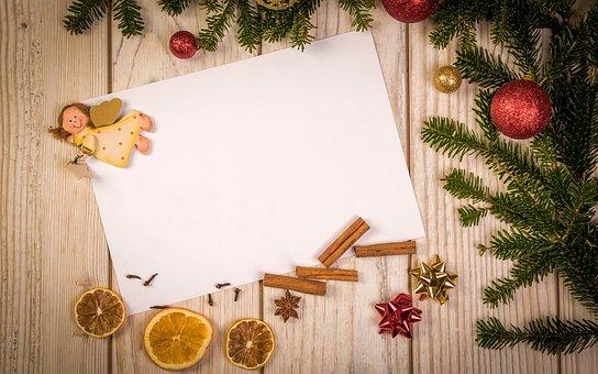 Dřevěné pozadí s volným listem papíru, zdobené andílkem, větvičkami, baňkami, skořicí a sušenými kolečky citrusu.