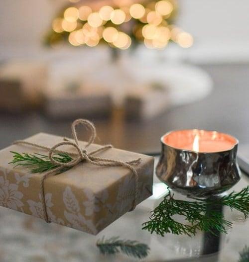 Béžový dárek, zdobený větvičkou, ležící vedle hořící stříbrné svíčky.