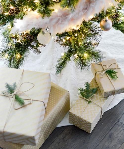 Pozadí s dárky v béžové barvě pod stromečkem, zdobené jehličnatými větvičkami.