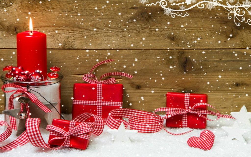 Pohlednice s červenými dárky a hořící červenou svíčkou před dřevěným pozadím.