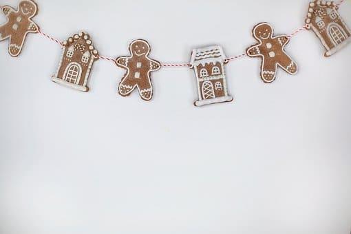 Bílé vánoční blahopřání s nitkou, spojující perníčky ve tvaru lidské postavy a domečku.