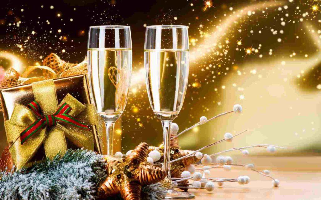 Zlaté pozadí s dárkem s červeno-zelenou mašlí a dvěma plnými sklenkami na šampaňské.