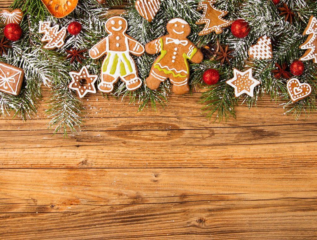 Dřevěné pozadí zdobené, v horní části, větvičkami, baňkami a perníčky s vánočními motivy.