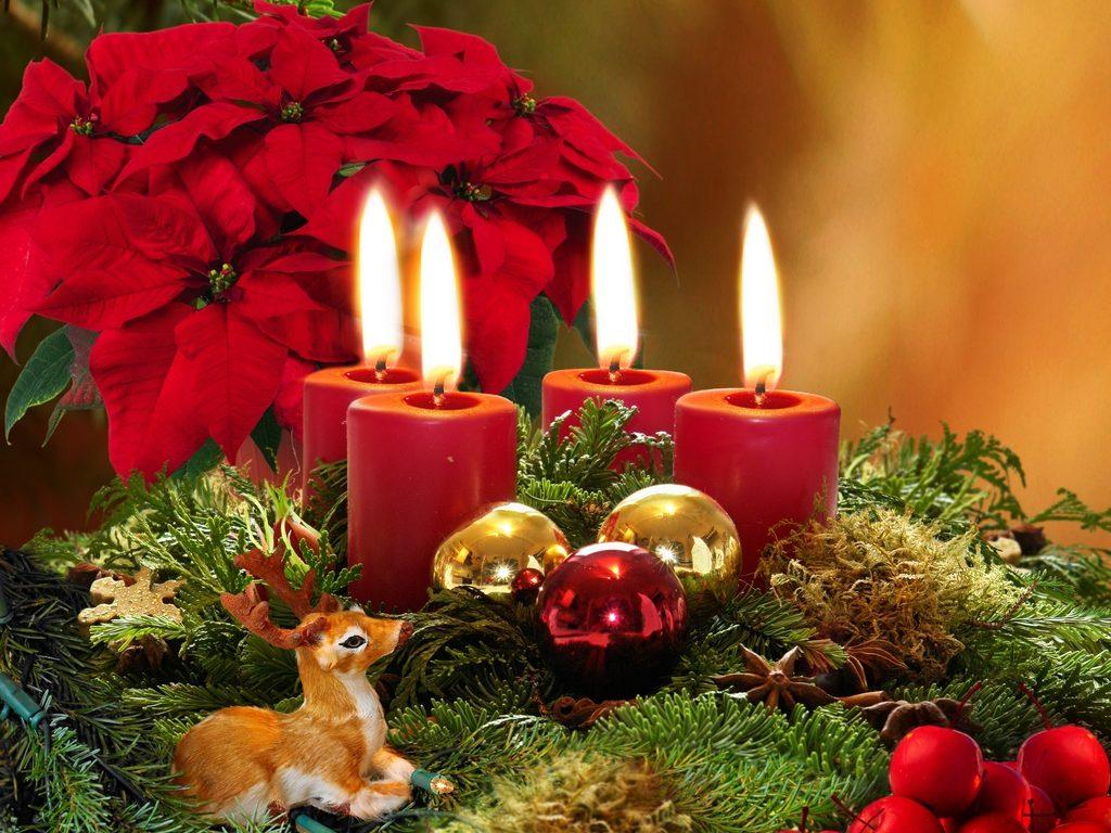 Adventní věnec se čtyřmi hořícími červenými svíčkami.