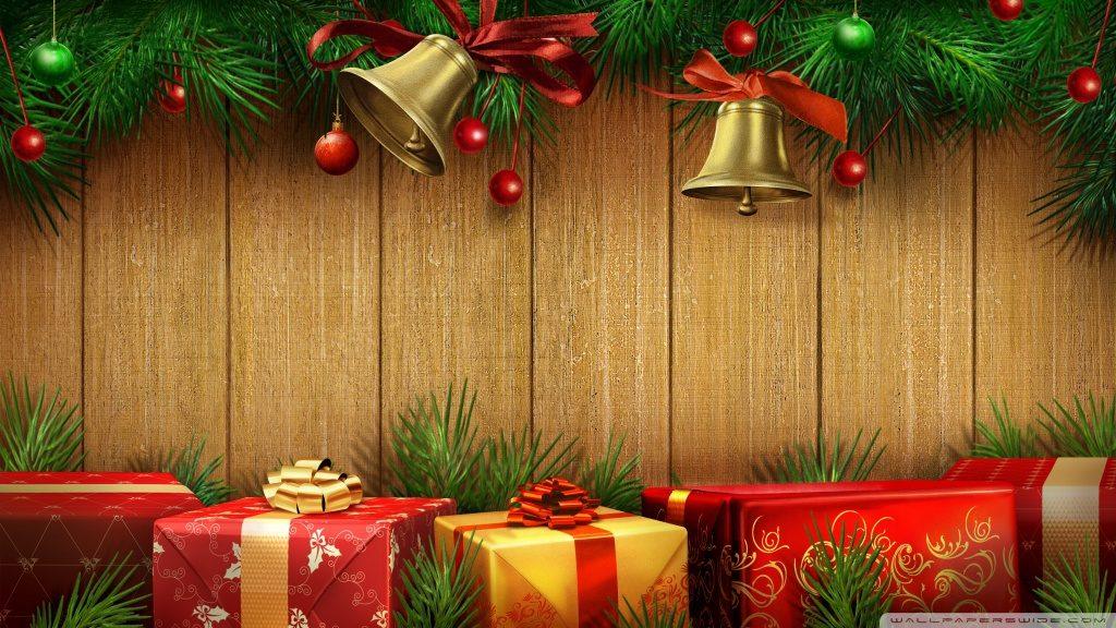 Dřevěné obrázkové pozadí zdobené, v horní části, větvičkami se zvony a ve spodní části barevnými dárky.