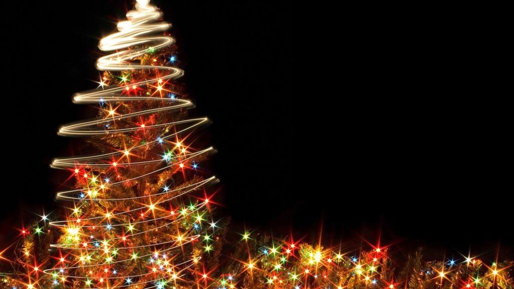 Barevně svítící vánoční strom na černém pozadí.