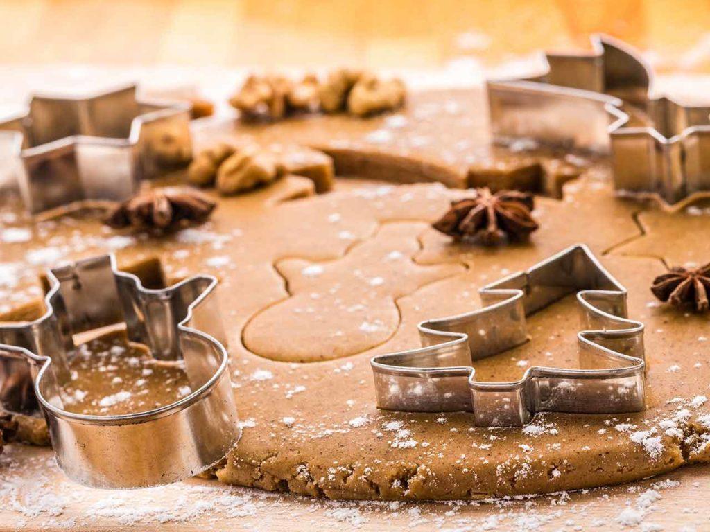 Vykrajované skořicové vánoční cukroví ve tvaru sněhuláků a stromečků.
