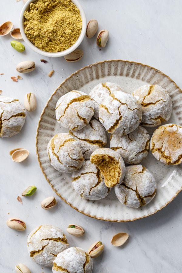 Cukroví z pistáciové mouky s popraskanými vrcholy, sypané cukrem.