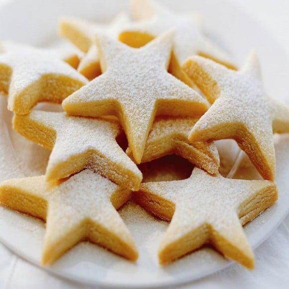 Dia cukroví ve tvaru hvězdiček na bílém talíři.