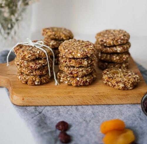 Nepečené sušenky s ovocem na dřevěném prkýnku.